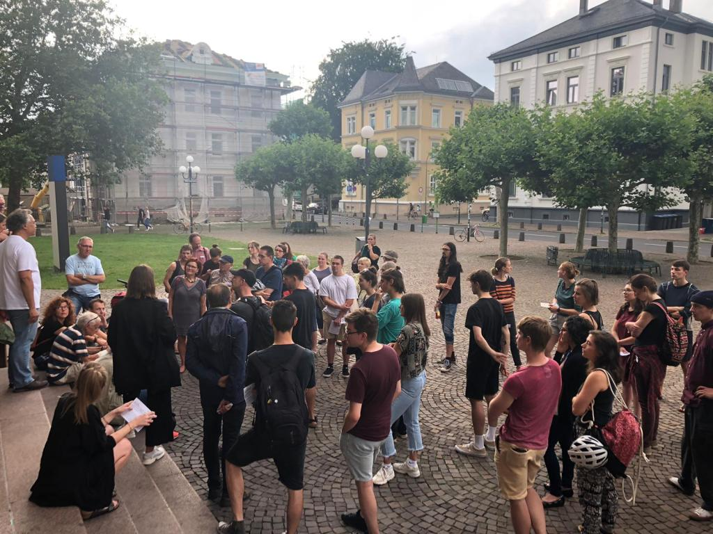 Participants of a postcolonial city tour assemble in front of Giessen University's Main Building in order to discover traces of the colonial past embedded in the spaces and places of the city.